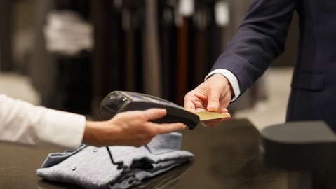 Shopping mall, close-up of business man in formal wear buying new cloths with credit card at luxury men clothing store