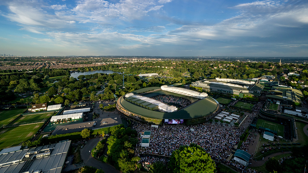 An aerial view overlooking the grounds with spectators on the Hill watching Cori Gauff (USA) play against Polona Hercog (SLO) on the big screen. The Championships 2019. Held at The All England Lawn Tennis Club, Wimbledon. Day 5 Friday 05/07/2019. Credit: AELTC/Joe Toth