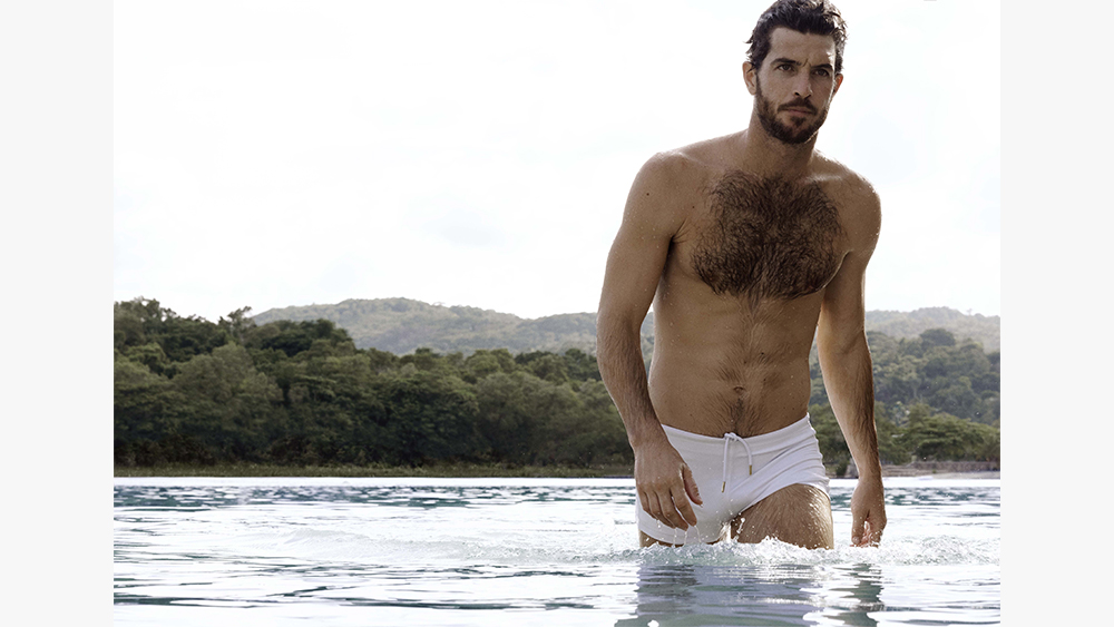 A model wears swim trunks from the new Orlebar Brown 007 collection.
