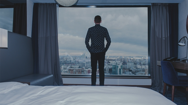 Young business man on the background of the panoramic windows with the view on the city from the hotel room.