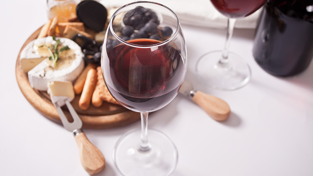Two glass of red wine and plate with assorted cheese, fruit and other snacks for party.