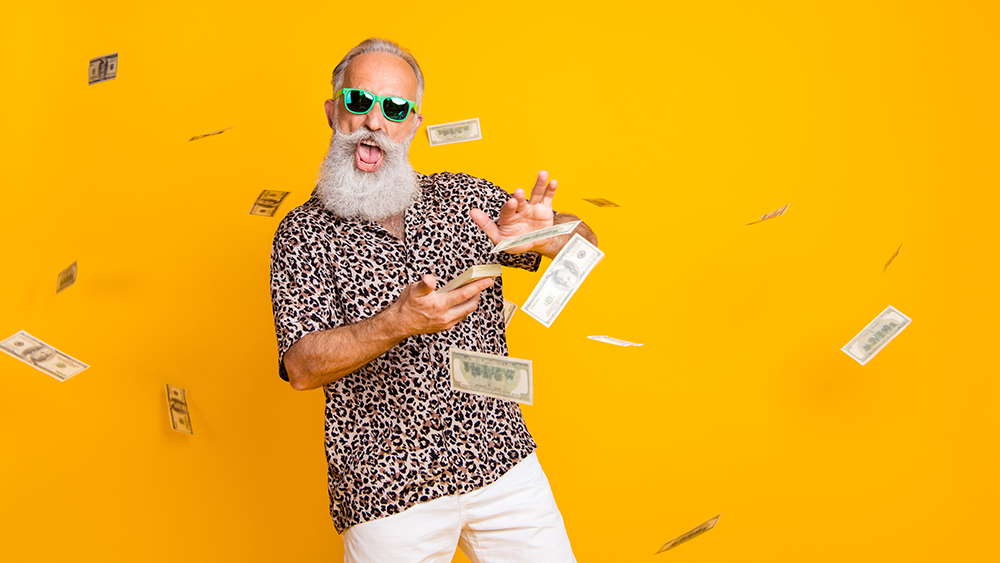 Portrait of crazy funny funky old long bearded man millionaire in eyewear, eyeglasses waste money throw banknotes wear leopard shirt shorts isolated over yellow background