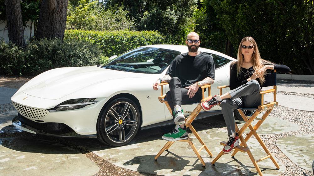 Adam Levine and Behati Prinsloo sit in front of a Ferrari Roma.
