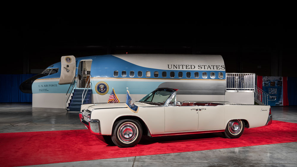A replica of Air Force One sits behind a 1963 Lincoln Continental Convertible used by John and Jackie Kennedy.