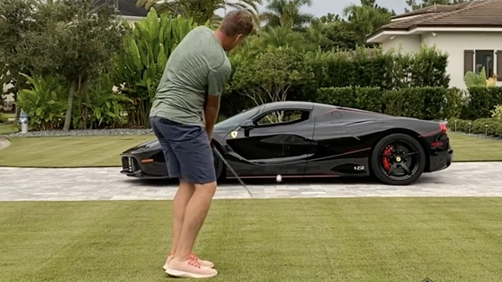Golfer Ian Poulter chips a golf ball through his LaFerrari Aperta