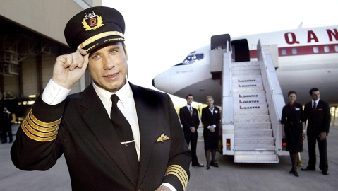 American movie srar John Travolta dips his hat during visit to Melbourne, Australia, Friday, July 4, 2003. Travoltais making a brief visit flying his own 707 jet,  to promote Qantas airline. (AP Photo/David Callow)