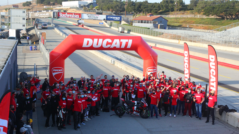 MotoAmerica star Kyle Wyman is flanked by attendees of the recent Ducati Revs event at Weathertech Raceway Laguna Seca.