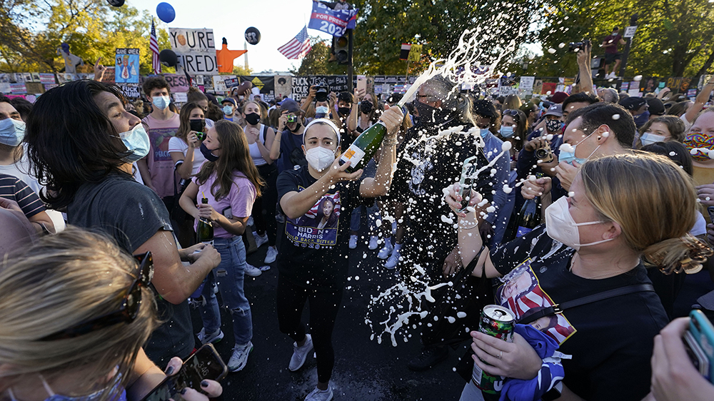 People spray champagne as they gather in Black Lives Matter Plaza to celebrate the presidential race being called in favor of Joe Biden over Pres. Donald Trump, Saturday, Nov. 7, 2020, in Washington. His victory came after more than three days of uncertainty as election officials sorted through a surge of mail-in votes that delayed the processing of some ballots. (AP Photo/Alex Brandon)