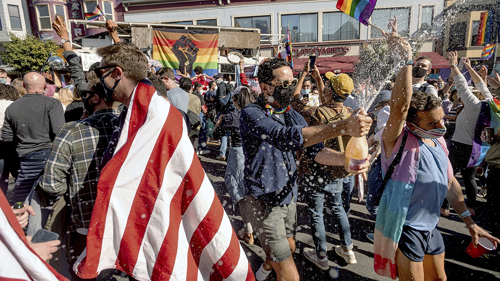Peter Puga sprays champagne while celebrating the victory of President-elect Joe Biden and Vice President-elect Kamala Harris in San Francisco's Castro district on Saturday, Nov. 7, 2020. (AP Photo/Noah Berger)