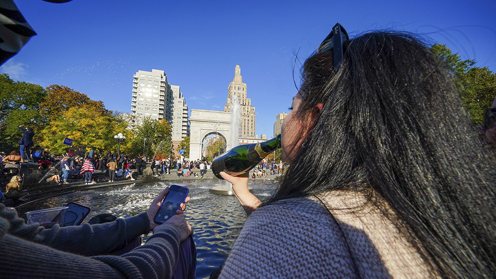 A woman is seen drinking from a champagne bottle as New York City erupts in celebration of Biden's win as the 46th U.S President at Washington Square Park in New York. (Photo by John Nacion / SOPA Images/Sipa USA)(Sipa via AP Images)