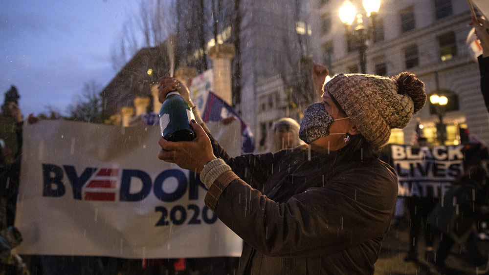 People flooded the streets opening up champagne to celebrate President-elect Joe Biden's win over President Donald Trump on Saturday in Portland, Ore. (AP Photo/Paula Bronstein)