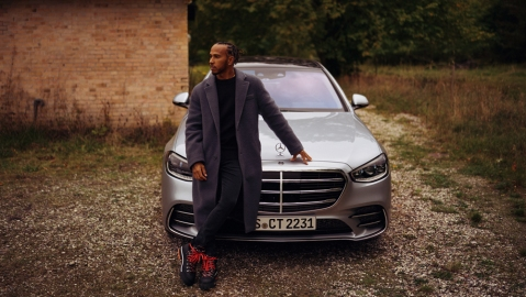 Formula 1 champion Lewis Hamilton stands by a new Mercedes-Benz S-Class.
