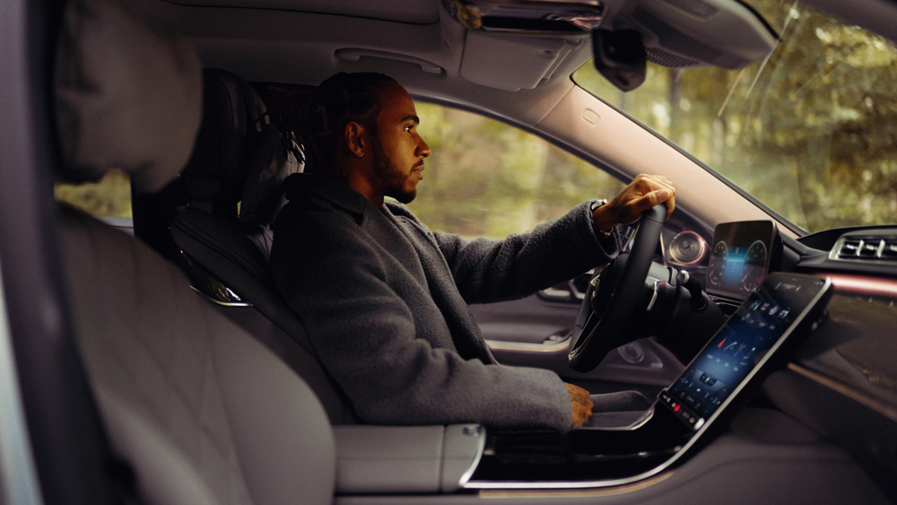 Formula 1 champion Lewis Hamilton sits in the driver's seat of a new Mercedes-Benz S-Class.