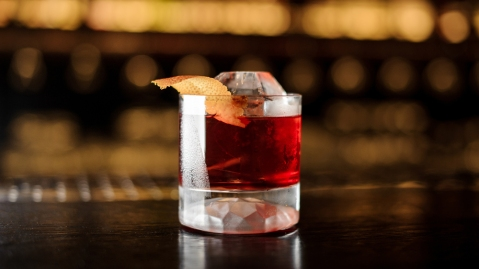 Glass of a Boulevardier cocktail with orange zest on the steel and wood bar counter bourbon
