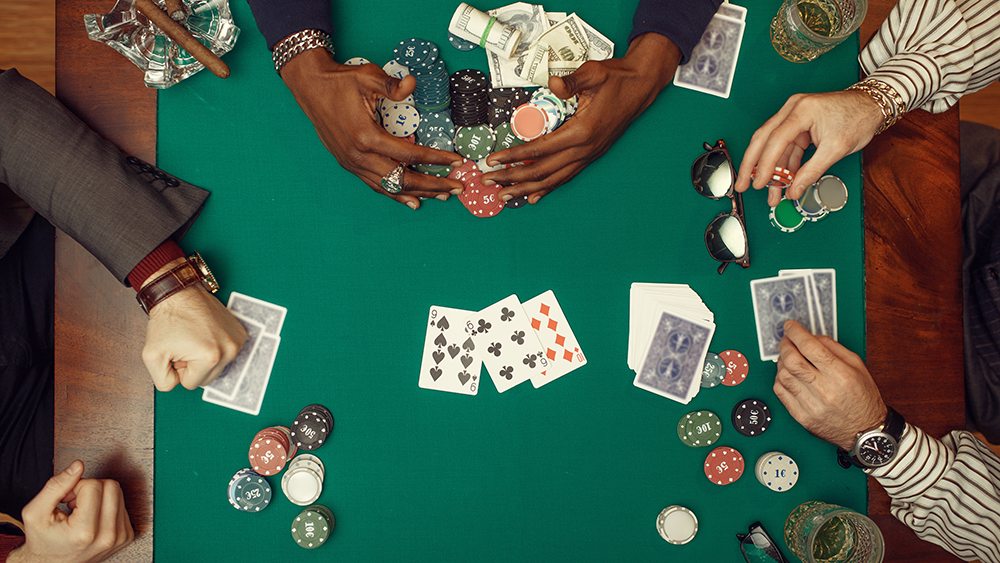 Poker players hands with cards, top view, gaming table with green cloth on background, casino. Games of chance addiction, risk, gambling house. Men leisures with whiskey and cigars