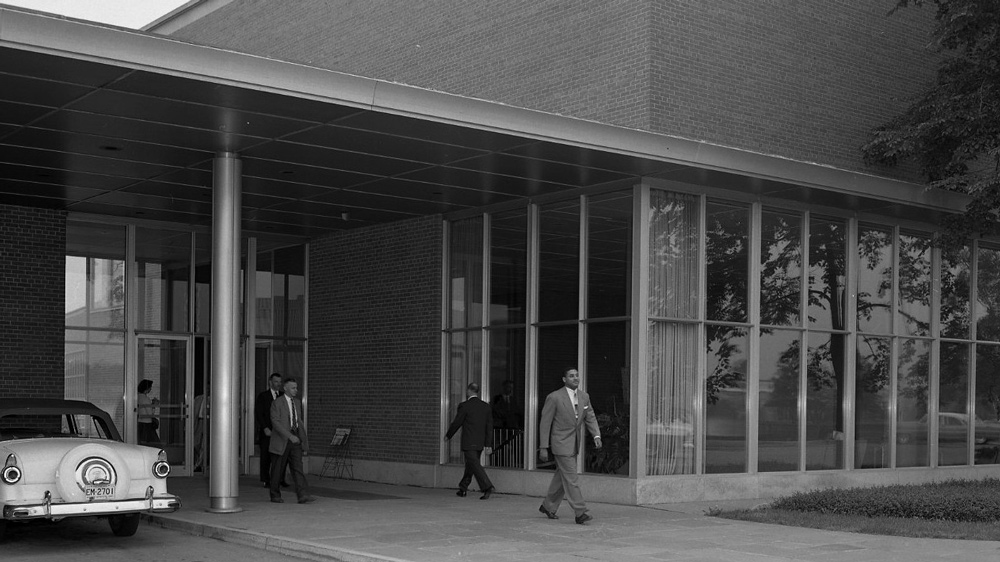 Automotive designer McKinley Thompson (foreground) walking in front of the Ford Product Development Center in Dearborn, Mich.