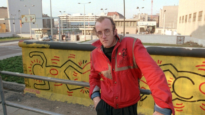 FILE - In this October 1986 file photo, artist Keith Haring stands in front of part of the Berlin Wall that he painted with a crawling baby in Berlin. The Berlin Wall came down in late 1989. Haring died of AIDS Feb. 16, 1990, at age 31.(AP Photo/Elke Bruhn-Hoffmann, File)