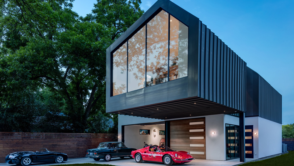 A Ferrari 246 GTS, Alfa Romeo Giulia and Porsche custom displayed in the driveway of a small home and large garage envisioned by Texas-based Matt Fajkus Architecture.