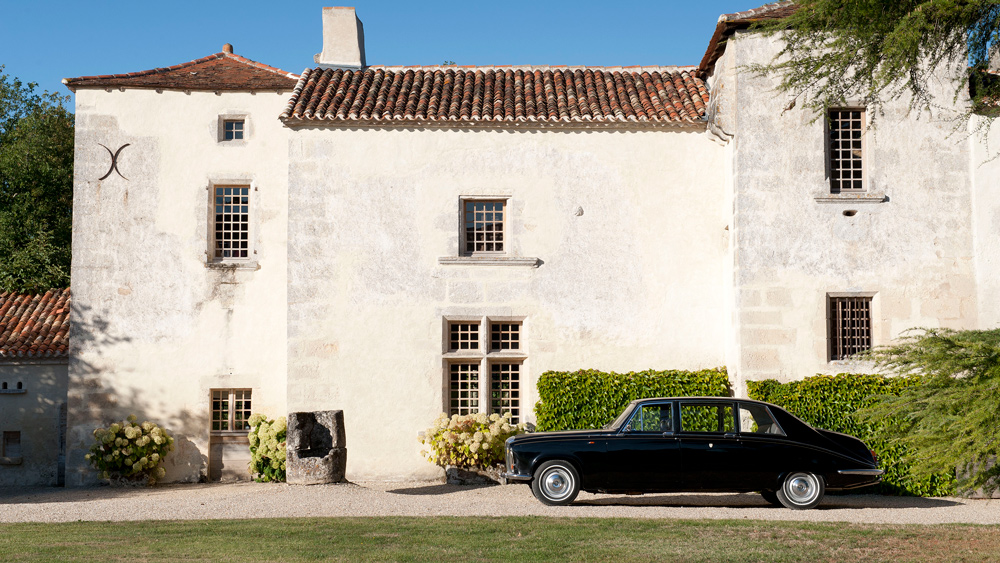 A Daimler DS 420 accents the Château de Puygaty in rural France.