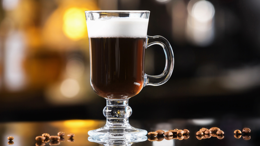 Closeup glass of irish coffee cocktail at bright bar counter background.