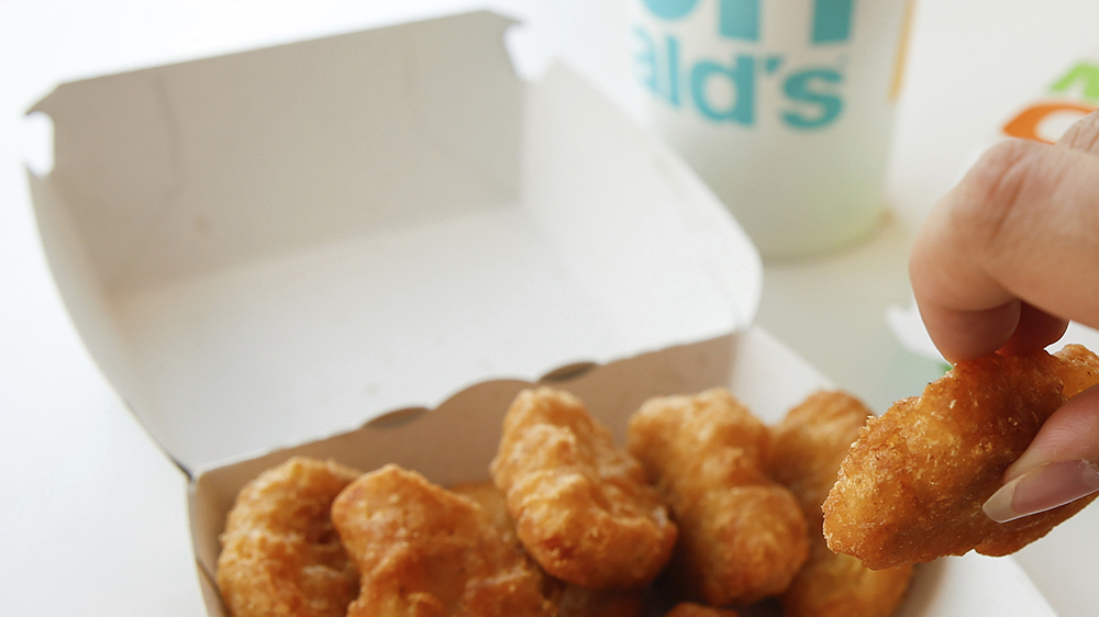 """28 June 2019, Germany (German), Berlin: A young woman eats from a cardboard box of Chicken McNuggets, taken at a McDonald's branch. The fast food chain McDonald's wants to produce less plastic waste. For example, desserts are to be sold in the course of the coming year in more sustainable packaging """"almost without plastic"""". Already this year plastic holders for balloons would be abolished, McDonald's announced. From 2021 they will no longer be allowed to be sold in the EU - as will disposable cutlery and plates and plastic straws. Photo by: Gerald Matzka/picture-alliance/dpa/AP Images"""