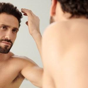 A model examining his hair.