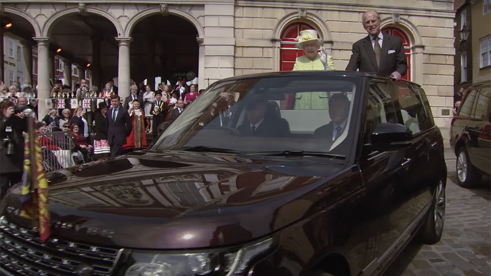 Queen Elizabeth and Prince Philip ride in a convertible Range Rover on the Queen's 90th birthday