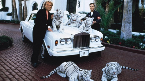 The magicians Siegfried & Roy pose with white tigers next to Roy horn's 1994 Rolls-Royce Corniche.