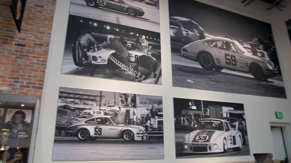 A wall of the Brumos Collection automotive museum with images of racing from Bill Warner.