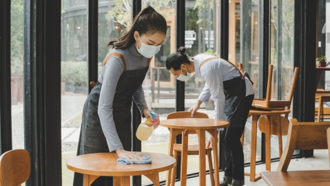 restaurant workers sanitizing tables