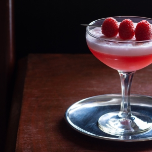 Clover Club Cocktail, a Sour Drink with Gin, Raspberries, and Egg White Foam in a Dark Luxurious Bar with Copy Space