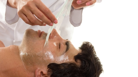 Facial Peel - A beautician performs a facial peel on a male client.