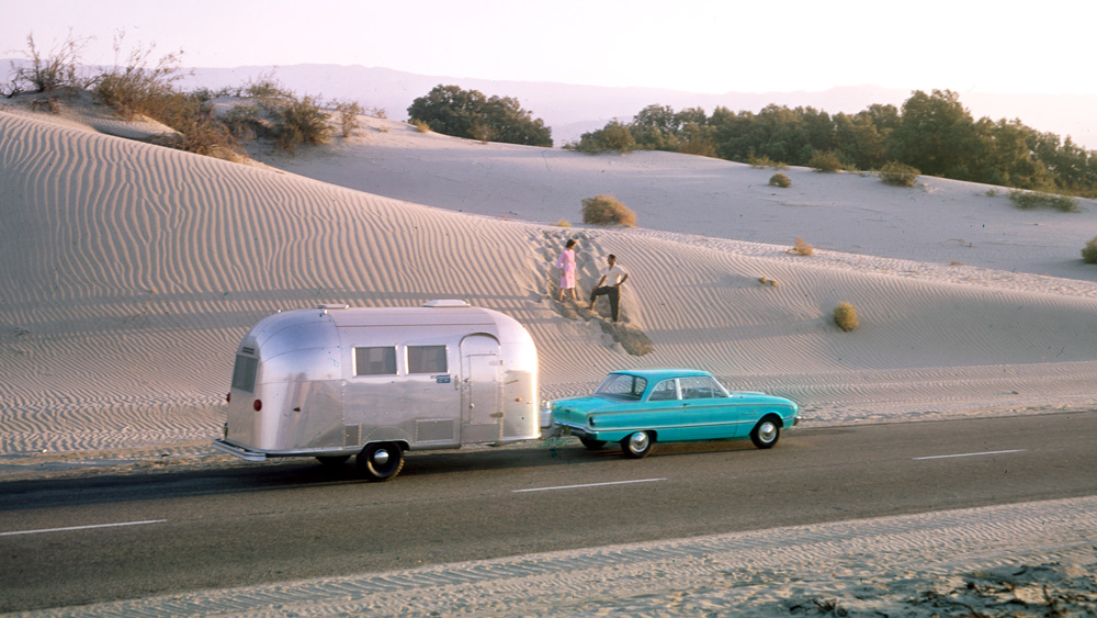 A couple head off the beaten path with their Airstream in tow toward the middle of last century.