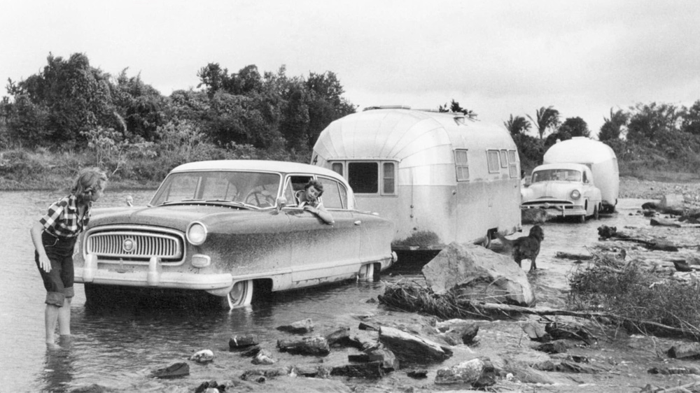 Travelers towing their airstream trailers navigate a muddy crossing.