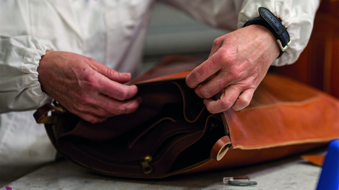 An artisan hand-crafting an Il Bisonte bag.