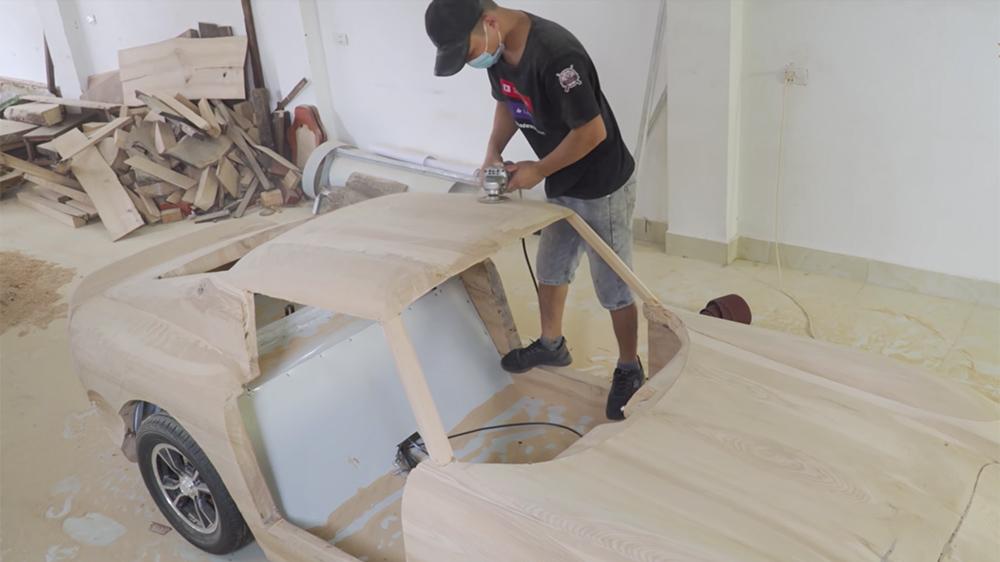 Trương Văn Đạo uses a disc scrubber to shape his wooden Ferrari 250 GTO