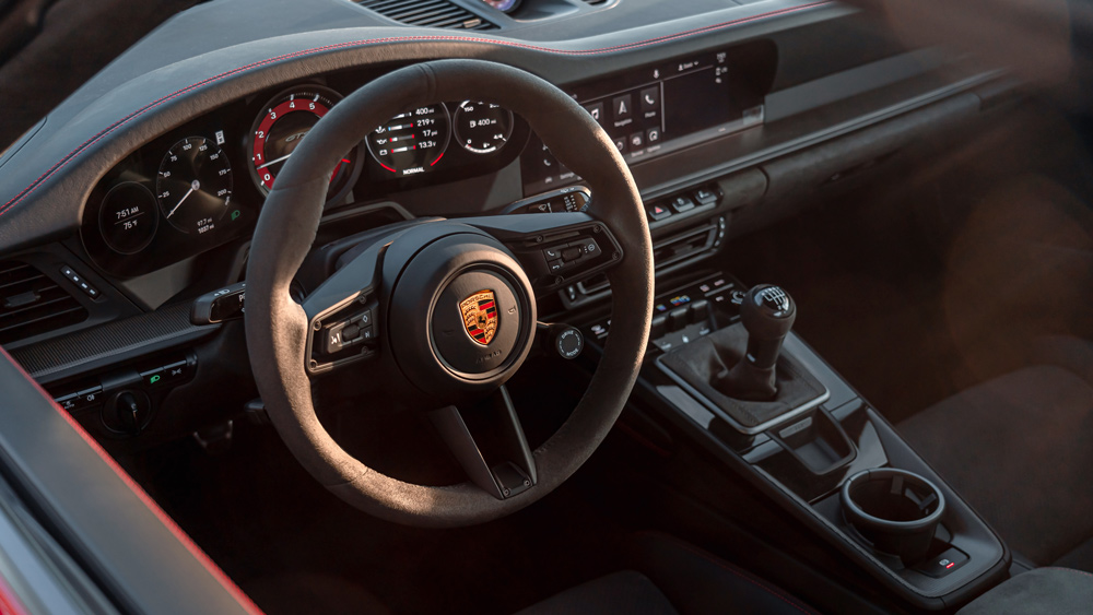 The steering wheel and dash of a 2022 Porsche 911 GTS.