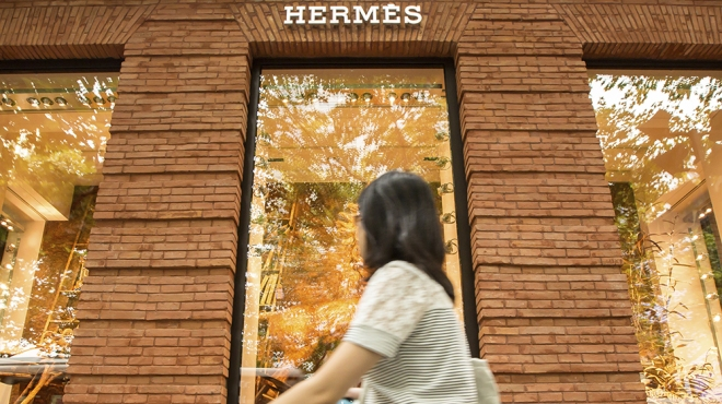 --FILE--A pedestrian walks past the Maison Hermes in Shanghai, China, 16 September 2014. Thriving demand in China boosted first-quarter sales at Birkin bag maker Hermes, underscoring an upbeat start to the year for some of the luxury sector's biggest names. From fashion labels to jewelers, many players in the industry have reported better-than-expected sales at the start of the year, with strong demand from Asian and US shoppers. Hermes, known for its ,000-plus hand-stitched Birkin and Kelly bags, said revenue rose 11 percent on a constant currency-basis from a year earlier, more than analysts had forecast.  (Imaginechina via AP Images)