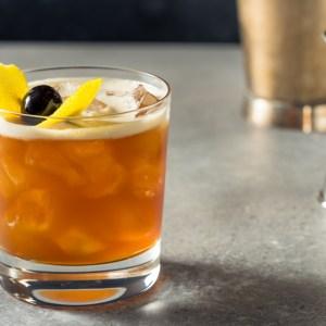 Amaretto Sour Cocktail in rocks glass on ice cherry garnish