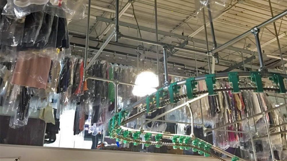 Dry cleaning hanging on Meurice's industrial conveyor belt.